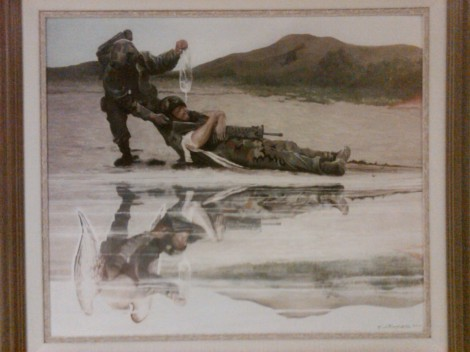 A  cleric hauling a wounded solider off the battlefield, his reflection  showing wings
