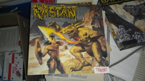 A boxed copy of the game Rastan, which shows a man with fire coming off his sword to strike a lizard-thing